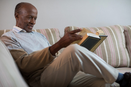 generation gap: Smiling senior man reading book while sitting on sofa at home