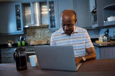 receding: Senior man using laptop at table in kitchen at home