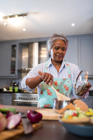 Senior woman making food in kitchen at home Stock Photo