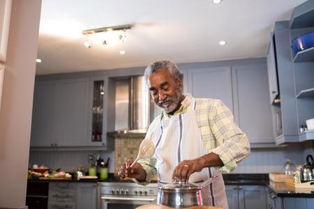 Smiling senior man preparing food in kitchen at home
