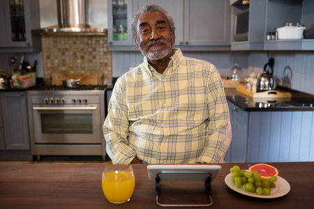 Portrait of smiling senior man in kitchen at home