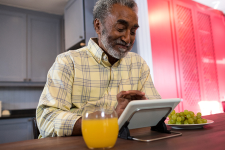 aplaudiendo: Happy senior man using tablet computer at table in kitchen