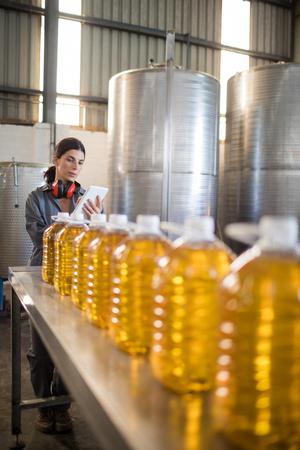 Female worker using digital tablet in oil factory