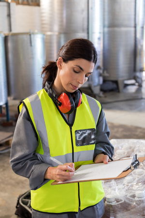 Female technician writing in clipboard at oil factory