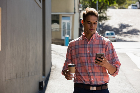frizzy: Young man using phone while walking by building in city Stock Photo