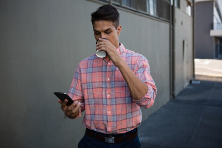 frizzy: Young man using mobile phone while having drink by wall