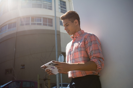 leaning on the truck: Side view of man reading paper while standing by wall