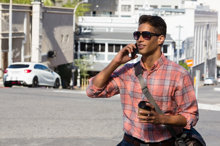 frizzy: Young man in sunglasses talking on mobile phone while walking on city street Stock Photo