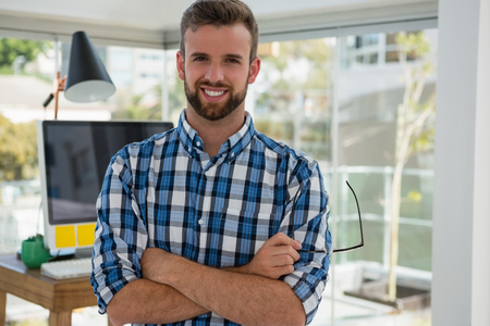 Portrait of smiling businessman with arms crossed standing in office Stock Photo