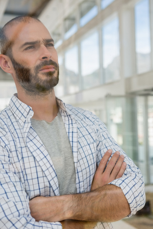Thoughtful male designer with arms crossed looking through window seen through glass