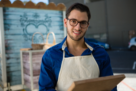Portrait of smiling owner holding writing slate while standing by food truck