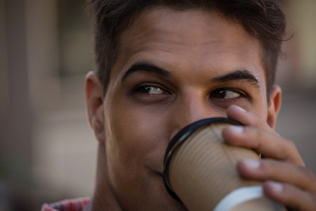 frizzy: Close up of young man looking away while having drink