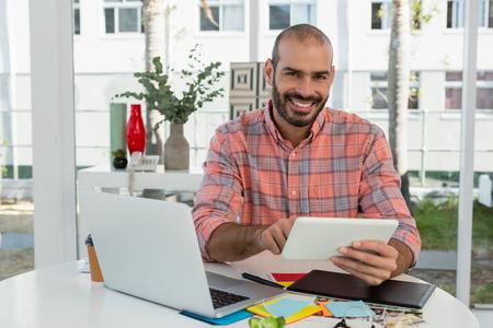 Portrait of smiling graphic designer using tablet at desk in office