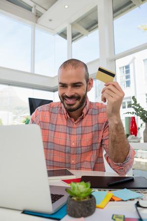 Smiling designer holding credit card while using laptop at desk in studio