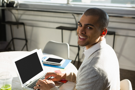 Portrait of businessman using laptop computer while sitting at desk in office Stock Photo