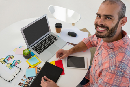 オフィスのデスクでタブレット コンピューターを使用してグラフィック デザイナーの高角度の肖像画
