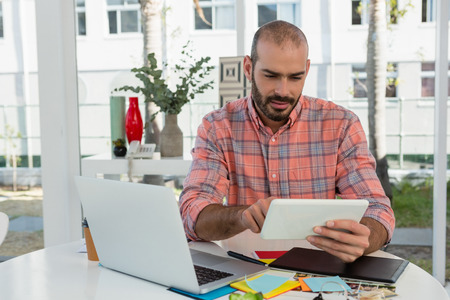 Graphic designer using tablet while sitting at desk in office Stock Photo