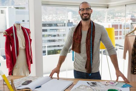 Portrait of fashion designer standing at table in studio