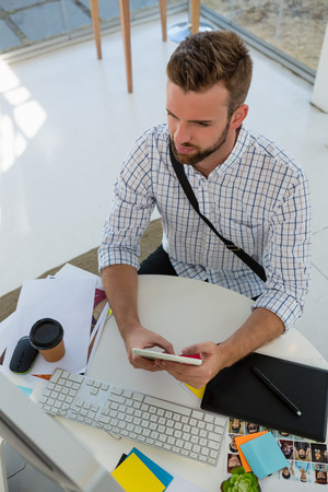 High angle view of graphic designer using tablet computer at desk in office