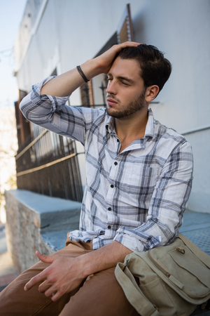frizzy: Tensed man with eyes closed sitting on retaining wall