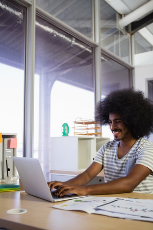 human likeness: Smiling young man using laptop at desk in creative office