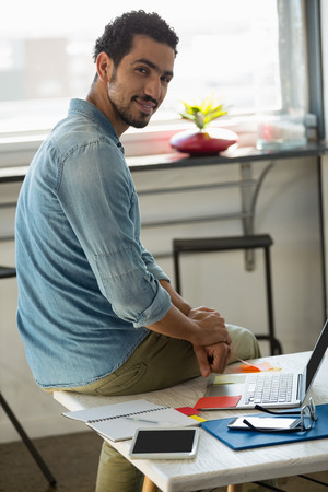 human likeness: Portrait of confident young man sitting on desk in office Stock Photo