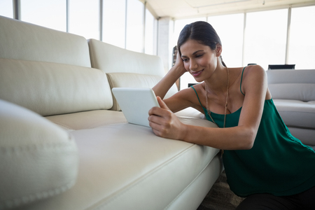 human likeness: Young woman using digital  tablet on sofa at office Stock Photo