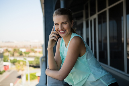 Portrait of happy young businesswoman talking on mobile phone in office balcony