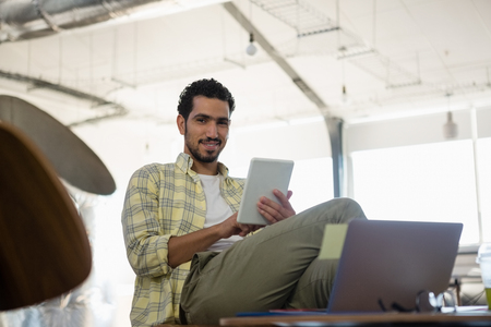 legs crossed at knee: Portrait of smiling young man using tablet in creative office
