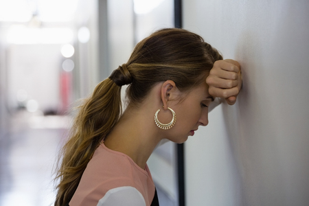desilusion: Sad young businesswoman leaning on wall at office Foto de archivo