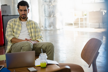 human likeness: Young man looking at laptop while relaxing in office Stock Photo