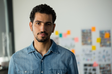 Portrait of confident young man standing in creative office
