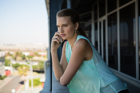 human likeness: Young businesswoman talking on mobile phone in office balcony