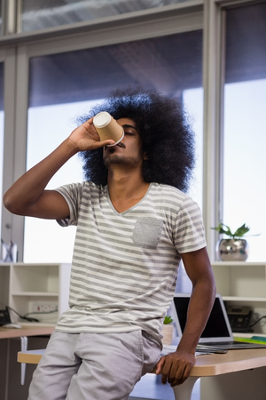 human likeness: Young man with curly hair drinking coffee at creative office