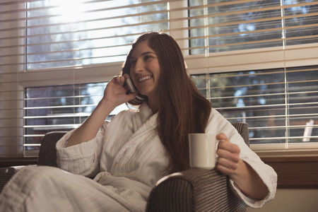 human likeness: Woman talking on mobile phone while having coffee in the living room at home