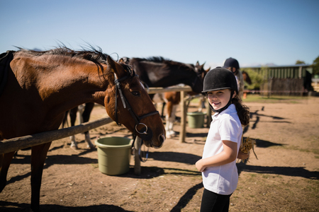 Smiling girl standing near the horse in ranch on a sunny day