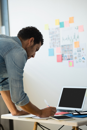 Concentrated young man working at desk in creative office Stock Photo