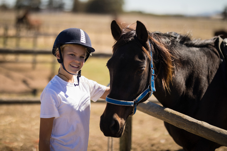 Portrait of smiling girl standing near the brown horse in the ranch Stock Photo