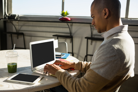 human likeness: Concentrated young man using laptop at desk in creative office
