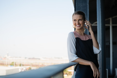 human likeness: Smiling young businesswoman talking on phone in balcony at office