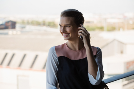 Happy young businesswoman talking on mobile phone in balcony at office