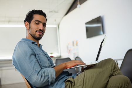 legs crossed at knee: Portrait of relaxed young man using laptop while sitting in office