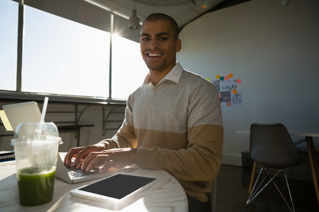 human likeness: Portrait of smiling young man using laptop at desk in offce