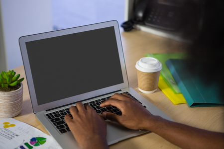 human likeness: Cropped image of man using laptop at desk in creative offce
