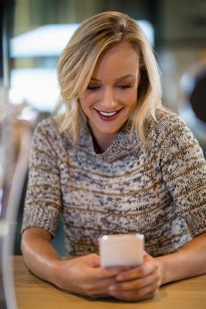 Smiling beautiful woman using mobile phone at bar counter