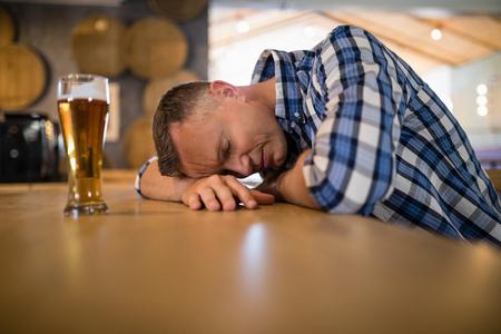 inebriated: Drunken man sleeping on counter in bar