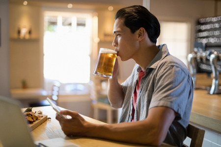 sample tray: Smiling man using digital tablet while having beer in restaurant
