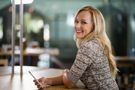 Portrait of smiling beautiful woman using mobile phone at bar counter