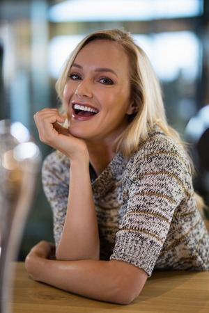Portrait of smiling beautiful woman sitting at bar counter Stock Photo