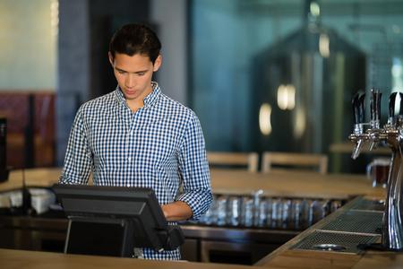 Barman werkende kassa in het restaurant Stockfoto
